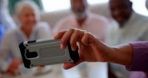 Gente mayor caucásica activa que toma el selfie con el teléfono móvil en la clínica de reposo 4k almacen de metraje de vídeo