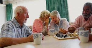 Gente mayor de la raza mixta activa que juega al juego de ajedrez en la clínica de reposo 4k almacen de metraje de vídeo