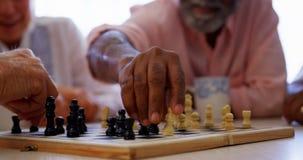 Gente mayor de la raza mixta activa que juega al juego de ajedrez en la clínica de reposo 4k almacen de video