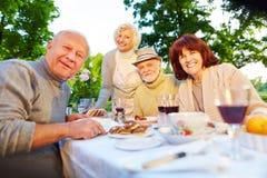 Gente mayor feliz que se sienta en la tabla del sistema en jardín Imágenes de archivo libres de regalías