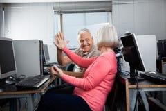 Gente mayor que da el alto cinco en clase del ordenador fotografía de archivo libre de regalías