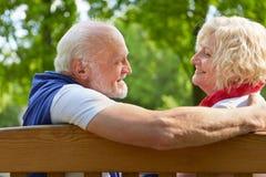 Gente mayor que habla y que liga en un banco de parque Imágenes de archivo libres de regalías