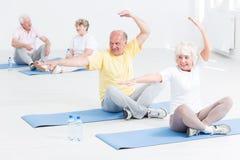 Gente mayor que hace ejercicios de la yoga Imagen de archivo