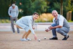Gente mayor que juega el boule que levanta encima de bolas Imagen de archivo