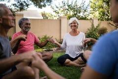 Gente mayor sonriente que medita con el instructor mientras que lleva a cabo las manos imagen de archivo