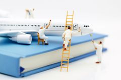 Gente miniatura: Aeroplano de la pintura del cepillo del equipo de los trabajadores foto de archivo