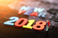 Gente miniatura: backpacker que mira el AÑO NUEVO 2018 del ` de la palabra Fotografía de archivo libre de regalías