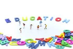 Gente miniatura: bambini e studente con l'inglese di legno variopinto Immagine Stock Libera da Diritti