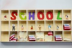Gente miniatura: bambini e studente con l'inglese di legno variopinto Fotografie Stock