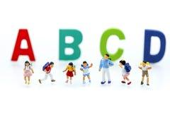 Gente miniatura: bambini e studente con l'inglese di legno variopinto Immagini Stock