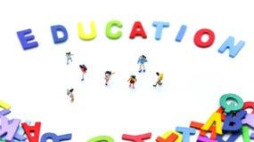 Gente miniatura: bambini e studente con l'inglese di legno variopinto Fotografia Stock