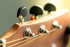 Gente miniatura: bambini e studente con la chitarra acustica, Ti Immagini Stock