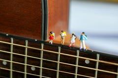 Gente miniatura: bambini e studente con la chitarra acustica, Ti Fotografia Stock Libera da Diritti