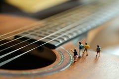 Gente miniatura: bambini e studente con la chitarra acustica, Ti Fotografie Stock Libere da Diritti