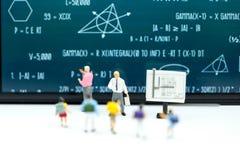 Gente miniatura: bambini ed insegnante con il BAC della lavagna di per la matematica Immagine Stock