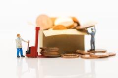 Gente miniatura: Camión de plataforma del uso del trabajador con la pila de monedas en la caja, usando como concepto del negocio  Foto de archivo libre de regalías