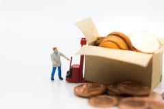 Gente miniatura: Camión de plataforma del uso del trabajador con la pila de monedas en la caja, usando como concepto del negocio  Imagenes de archivo
