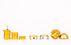 Gente miniatura che lavora con l'uovo dell'oro Fotografia Stock Libera da Diritti