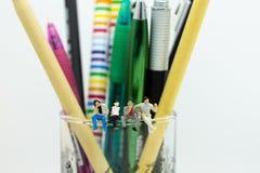 Gente miniatura che si siede con gli strumenti per imparare Uso di immagine per istruzione, concetto di affari immagini stock
