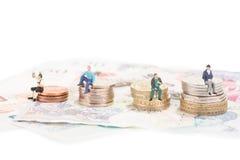 Gente miniatura che si siede sul primo piano delle monete fotografia stock libera da diritti