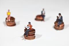 Gente miniatura che si siede sulle monete fotografia stock