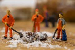 Gente miniatura che spala neve dal bordo Immagini Stock Libere da Diritti