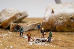 Gente miniatura che spala neve dal bordo Fotografia Stock