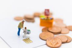 Gente miniatura con el carro de la compra usando como concepto del negocio del fondo Foto de archivo libre de regalías