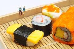 Gente miniatura con el sushi Foto de archivo libre de regalías