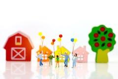 Gente miniatura con la familia que sostiene el globo con las casas, felices imagen de archivo libre de regalías