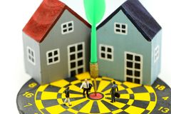 Gente miniatura: Condizione dell'uomo d'affari al centro del bersaglio con la casa come affare della proprietà di risultato di sc fotografie stock libere da diritti