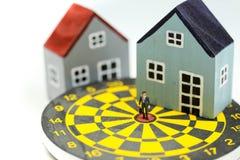 Gente miniatura: Condizione dell'uomo d'affari al centro del bersaglio con la casa come affare della proprietà di risultato di sc fotografie stock