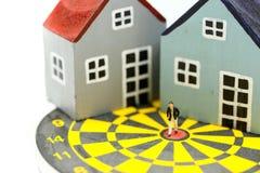 Gente miniatura: Condizione dell'uomo d'affari al centro del bersaglio con la casa come affare della proprietà di risultato di sc immagine stock