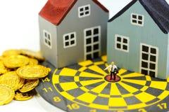 Gente miniatura: Condizione dell'uomo d'affari al centro del bersaglio con la casa come affare della proprietà di risultato di sc fotografia stock