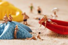 Gente miniatura in costume da bagno sulla spiaggia Immagine Stock Libera da Diritti