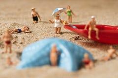 Gente miniatura in costume da bagno sulla spiaggia Fotografia Stock Libera da Diritti