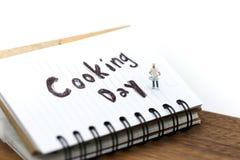 Gente miniatura: cuoco unico che cucina usando per il concetto di cottura del giorno immagine stock libera da diritti