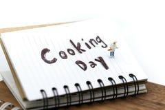 Gente miniatura: cuoco unico che cucina usando per il concetto di cottura del giorno immagine stock