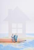 Gente miniatura della famiglia che si siede sul pecil con la casa sulla mappa di mondo Fotografie Stock Libere da Diritti