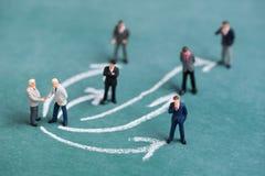 Gente miniatura di affari che stringe mano con la linea connett. della freccia di collegamento fotografia stock