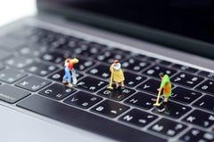 Gente miniatura: Domestica o casalinga che pulisce un computer portatile fotografie stock libere da diritti