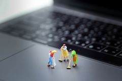 Gente miniatura: Domestica o casalinga che pulisce un computer portatile fotografia stock