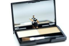 Gente miniatura: Domestica prodotti di bellezza di pulizia con il cosmetico fotografia stock