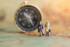 Gente miniatura: el hombre de negocios que se coloca en un mapa del mundo, tiene compás para el fondo, usando como concepto del n Foto de archivo libre de regalías