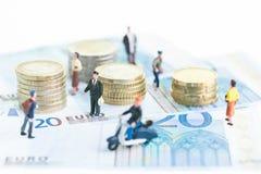 Gente miniatura en 20 billetes de banco euro y monedas euro Foto de archivo