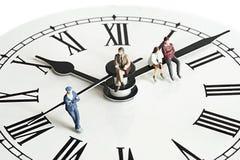 Gente miniatura en el reloj Imágenes de archivo libres de regalías