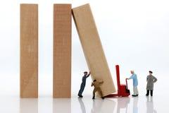Gente miniatura: Equipo de los trabajadores que para el efecto de dominó, foto de archivo