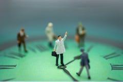 Gente miniatura: Equipo del hombre de negocios con el reloj El uso de la imagen toma tiempo para beneficiarse imagenes de archivo