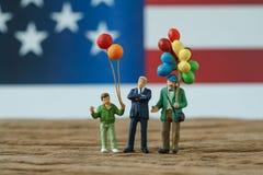 Gente miniatura, familia americana feliz que lleva a cabo la situación del globo Fotografía de archivo
