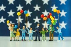 Gente miniatura, familia americana feliz que sostiene el globo con Uni Imagen de archivo libre de regalías